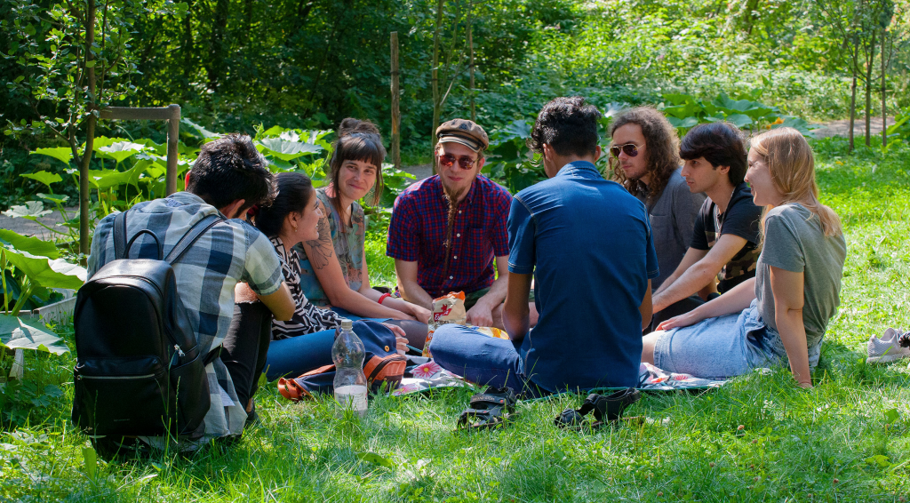 Ryhmä ihmisiä istuu ulkona keskustelemassa.
