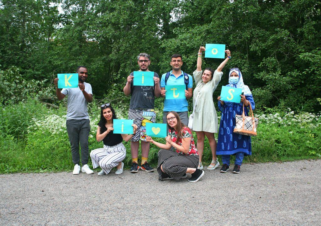 Ryhmän osallistujat kiittävät korteilla, joissa kiitos-sanan kirjaimet.